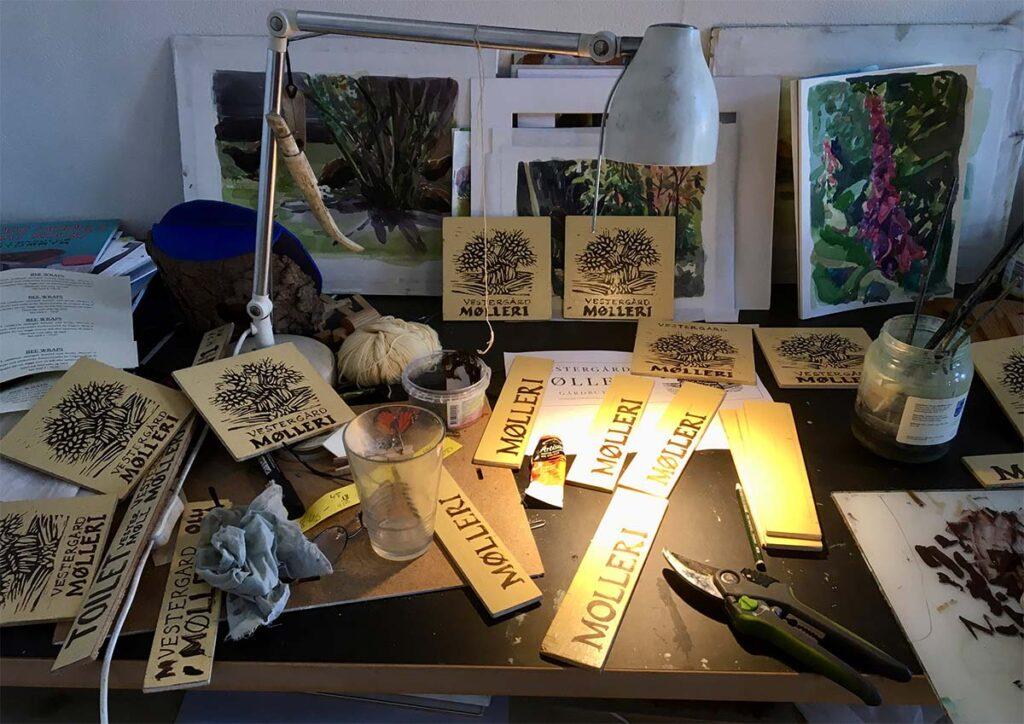 Arbejdsbord i atelier med håndmalede skilt til mølleriet.