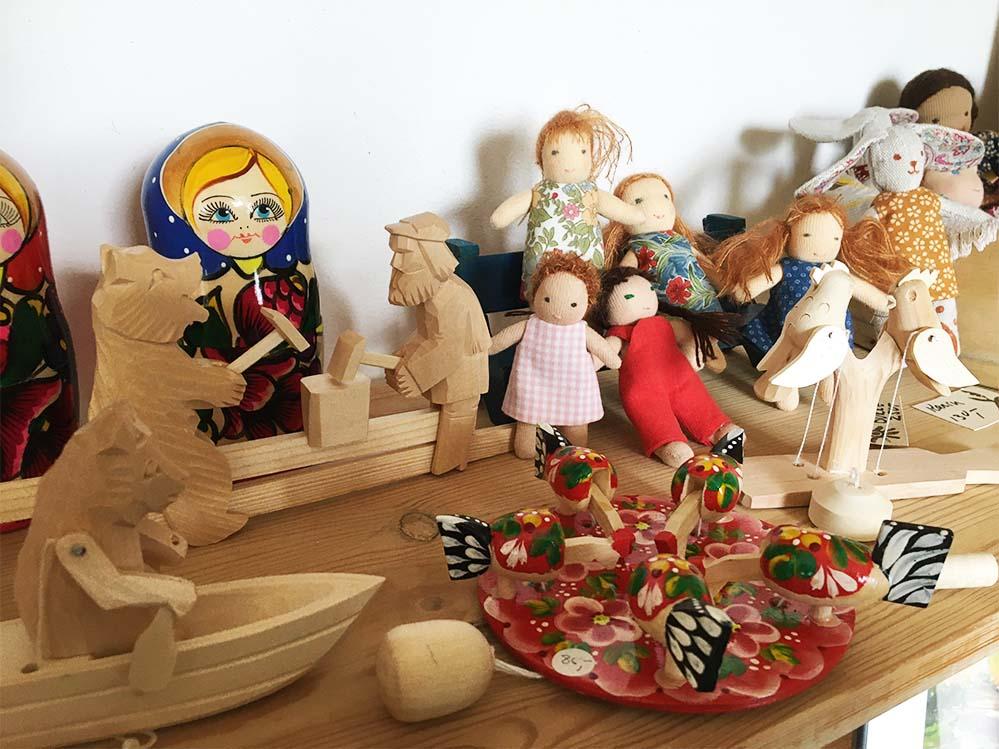 Russiske trælegetøj og håndsyede dukker på hylden i gårdbutikken.