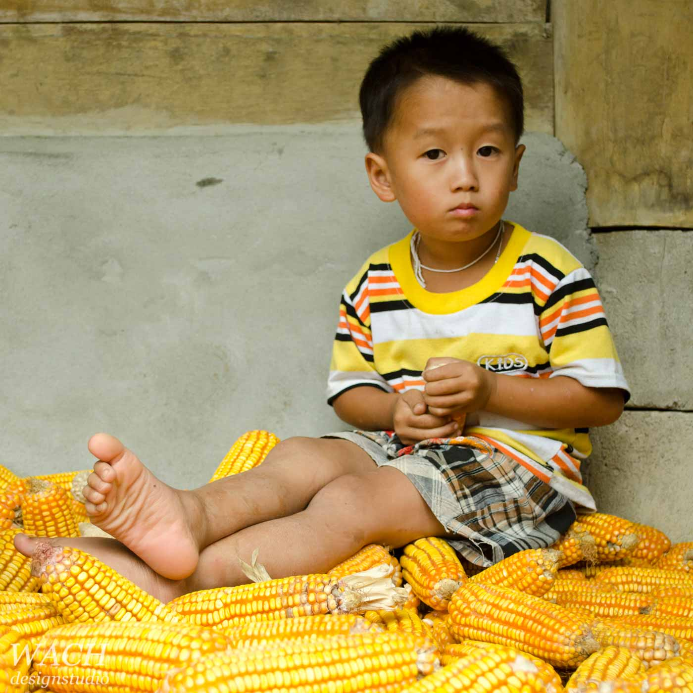 Boy in a Hmong village playing with harvested corn