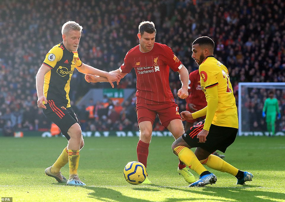 Watford midfielders Will Hughes and Etienne Capoue are involved in a tussle for the ball with Liverpool left back Milner