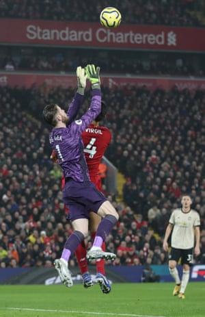 Manchester United's David de Gea jumps with Liverpool's Virgil van Dijk.
