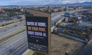 A sign near a Los Angeles freeway encourages people to stay at home to slow the spread of coronavirus.