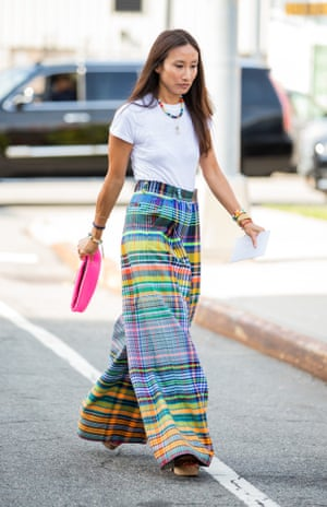 Elizabeth von der Goltz crossing a road in New York wearing multi-coloured plaid trousers and a white T-shirt