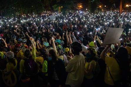 Protesters hold cellphone lights as they gather at the justice center and courthouse as feds attempt to intervene after weeks of protests in Portland.