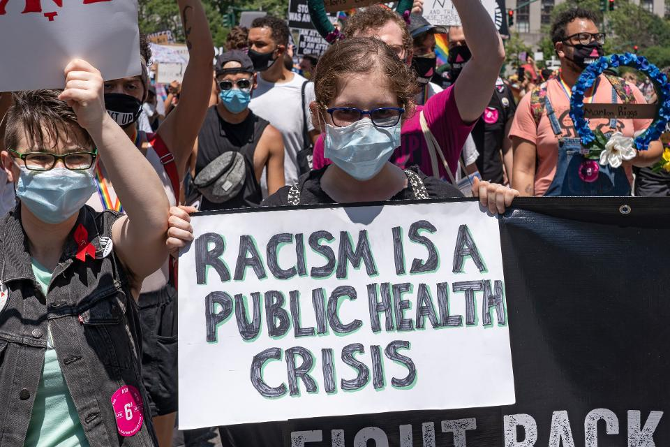 A participant holds a placard that says Racism is a public...
