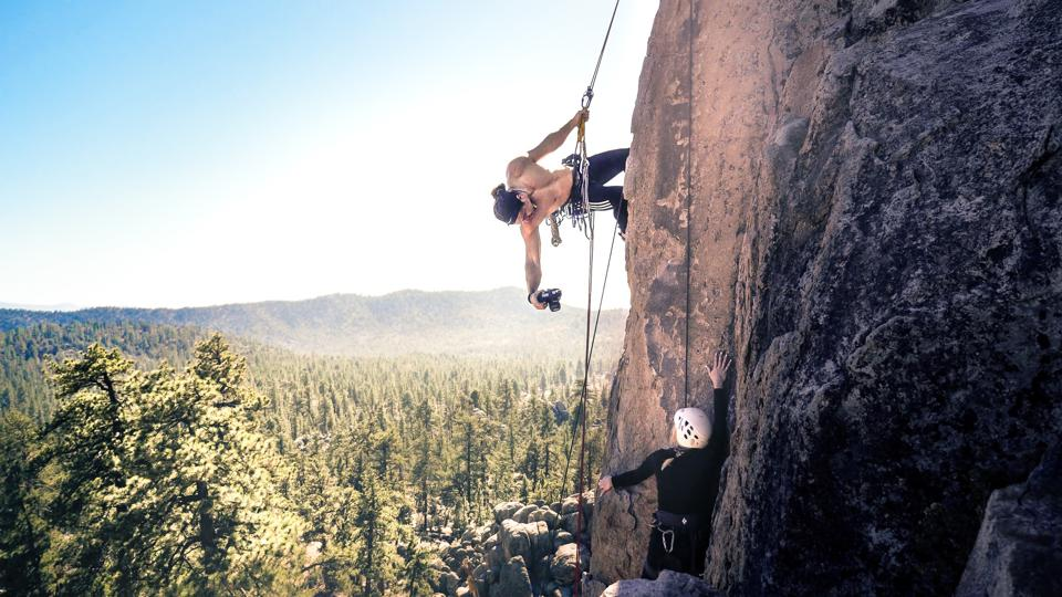 A young man holds a camera while attached to a rock climbing rope on a cliff.