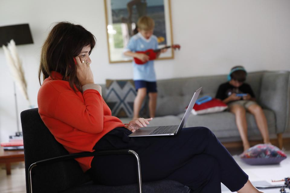 A woman works on her laptop in her living room while two children play in the background.