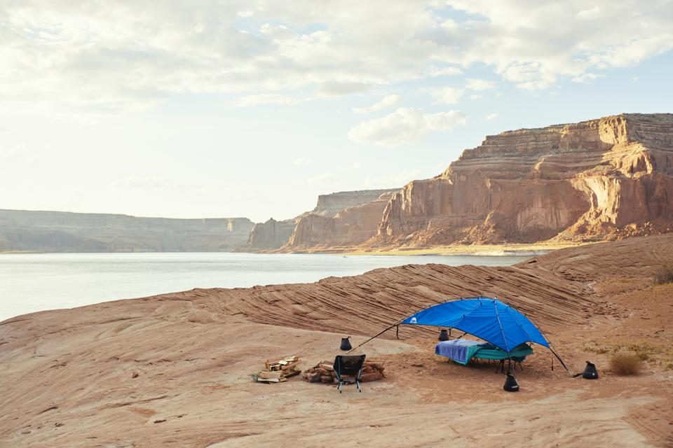 A campsite beside a desert lake lined with canyons.