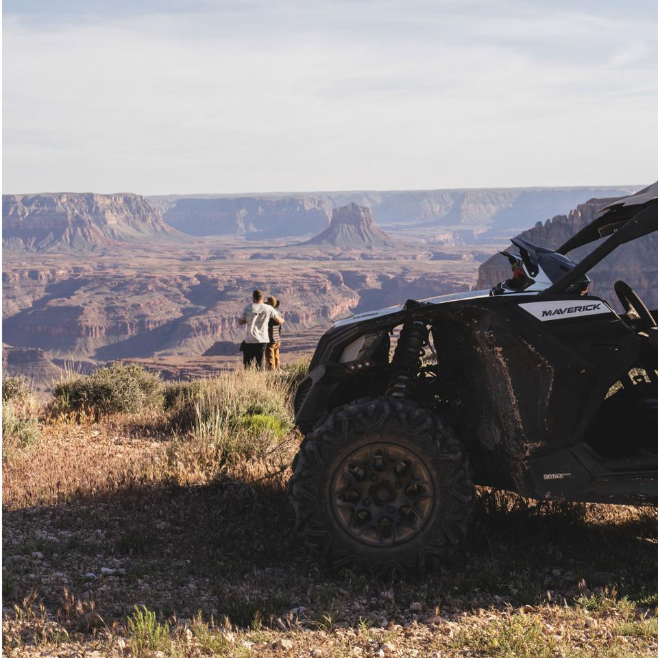 A couple stands in front of an ATV at the Grand Canyon.