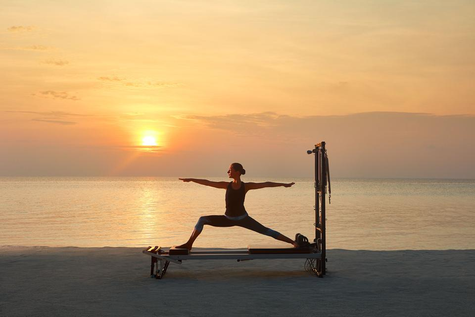 A woman performing yoga on the beachfront at One&Only Reethi Rah resort