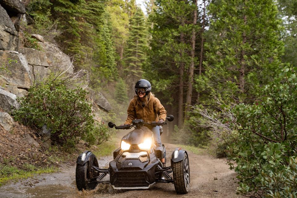 A young woman rides an ATV down a dirt road in a forest.