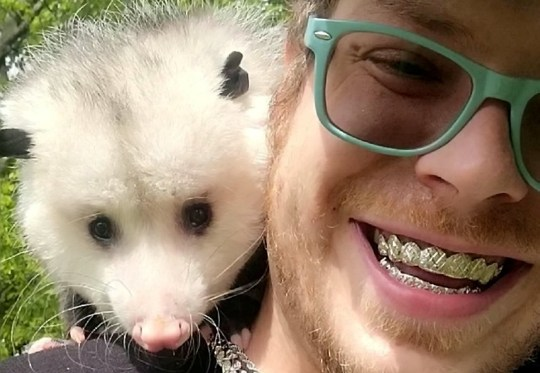 Kyle Fahye and his opossum Opie.
