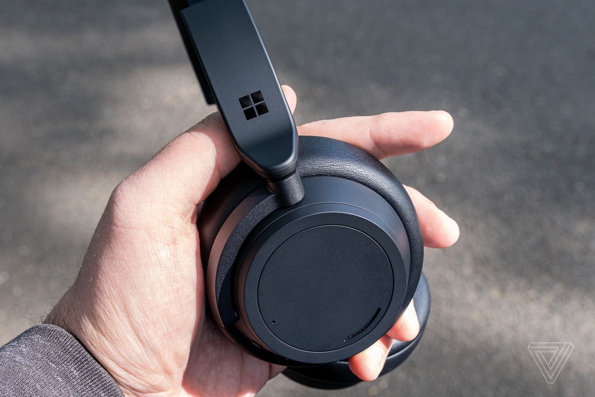 The matte black Surface Headphones 2 pictured in the reviewer's hand.