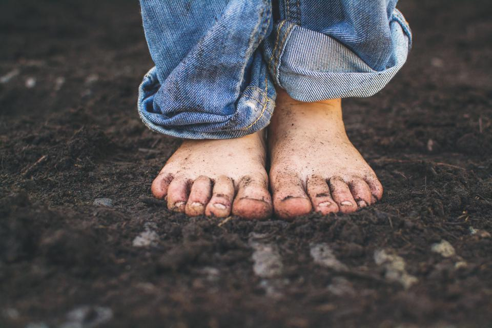Close-up of bare feet standing on dark soil.