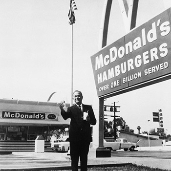 Ray Kroc, founder and chairman of McDonald's Corporation, stands outside one of his franchises, holding a hamburger and a drink, circa 1960.