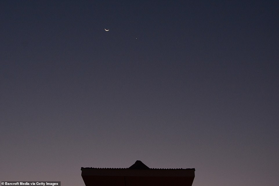 While Venus and the Moon may look within touching distance, they are actually separated by around 67 million miles. Pictured, the event this morning from Turkmenistan