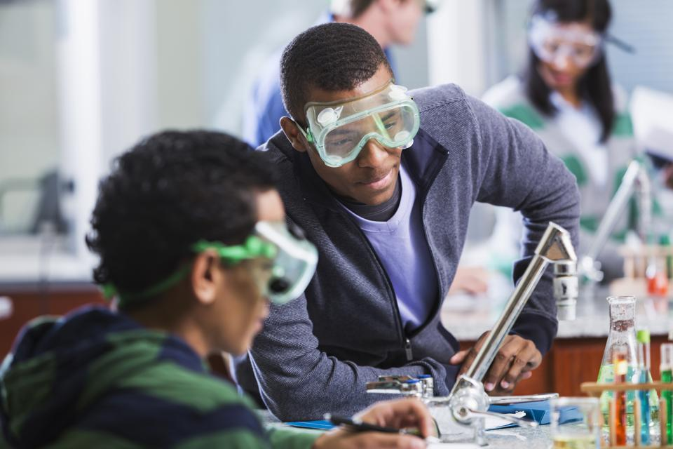 Multi-ethnic students wearing safety glasses in chemistry class