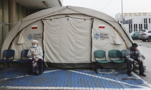 People sit outside a medical tent used for COVID-19 testing near a hospital in Warsaw, Poland, on Wednesday, 4 November, 2020.