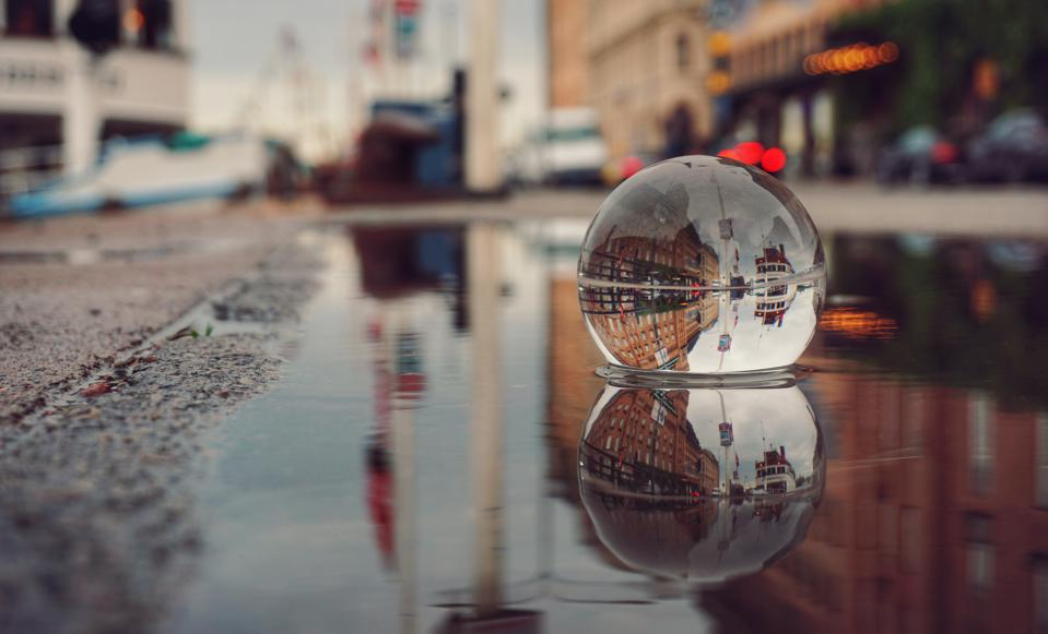 Reflection Of Buildings On Wet Street In City