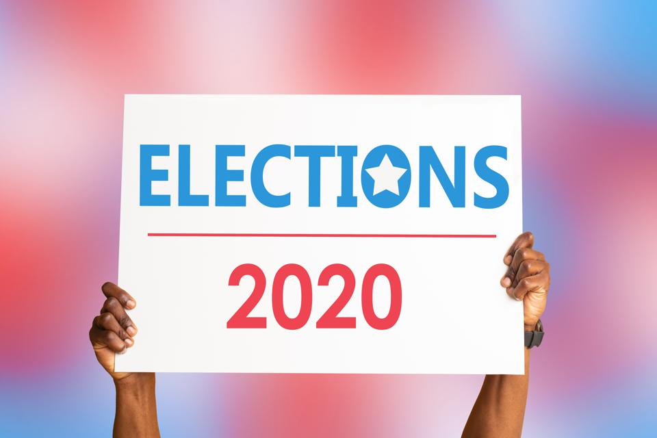 African American citizen holding sign that says ELECTIONS 2020 on colorful background, closeup