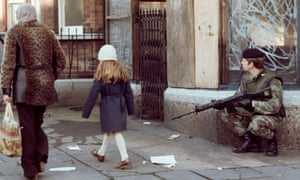 A woman and child walk past a British soldier on patrol in the New Lodge district of Belfast in 1978.