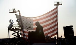 Donald Trump is seen in silhouette against a US flag as he speaks at a rally on September 18, 2020.