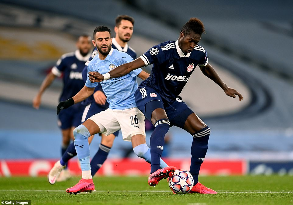 Pape Abou Cisse of Olympiacos is challenged for the ball by Manchester City midfielder Riyad Mahrez in the second half