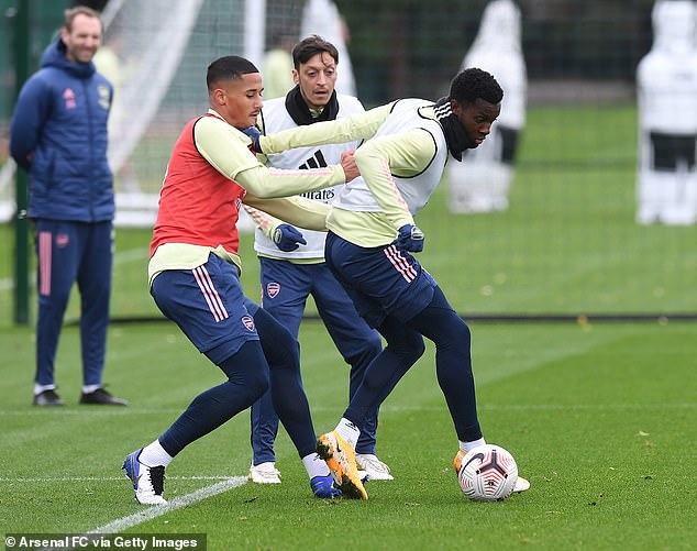 Saliba challenges Eddie Nketiah in training last month as Mesut Ozil watches on