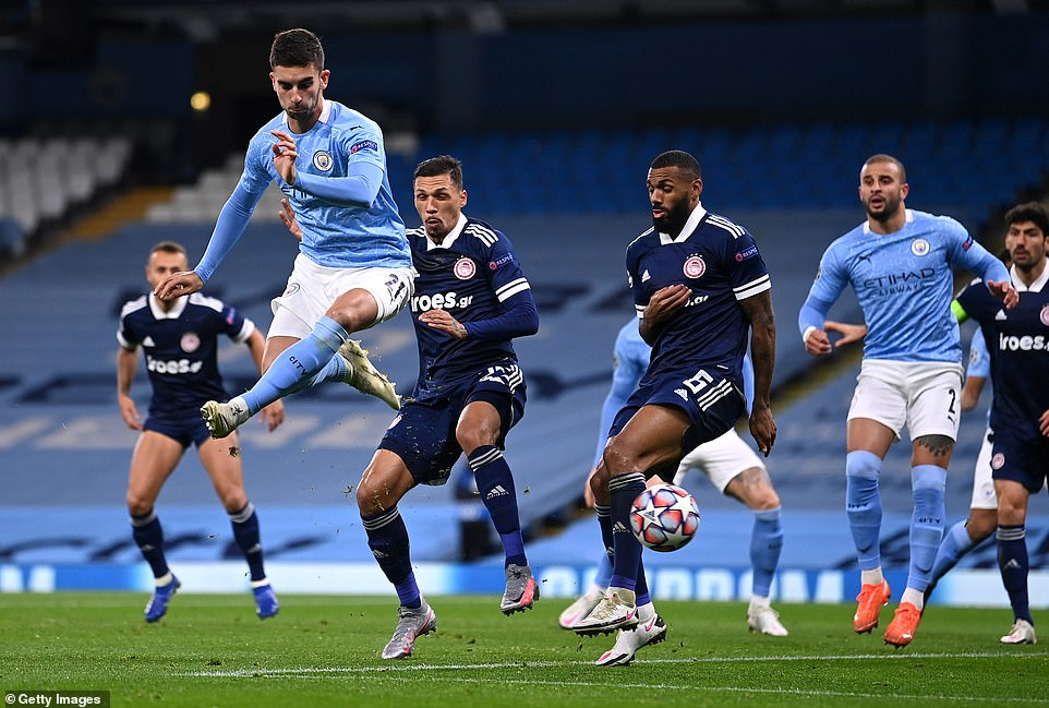 Manchester City's Torres rises up in the box to win the ball ahead of Olympiacos' Yann M'Vila during the first half