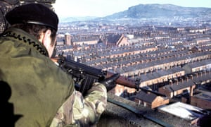 A British soldier takes aim at a suspect from an army observation post overlooking the New Lodge area of Belfast in February 1978.