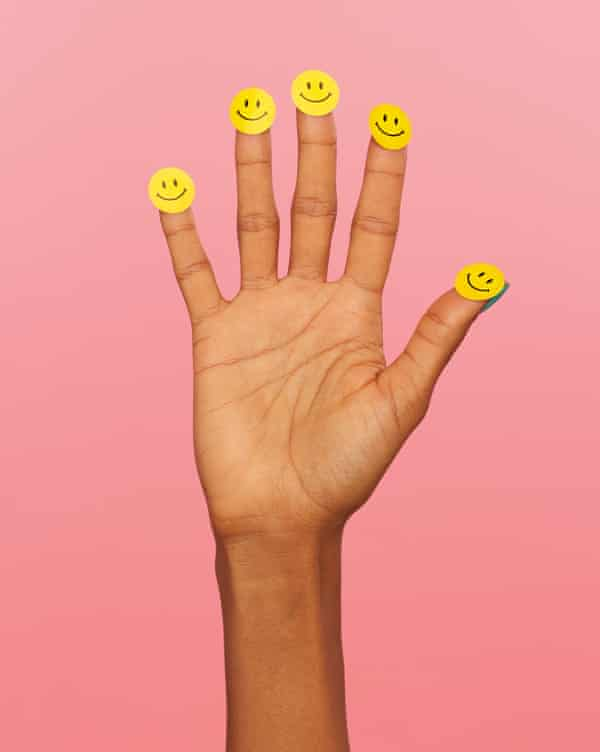 Hand with smiley stickers on fingers and thumbs, against pink background
