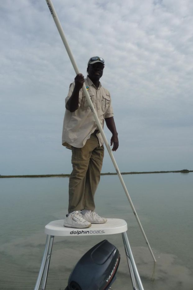 Resident Gillie Ishi, slowly and silently sculling the 17ft stiff-pole as he peers the shallows for bonefish