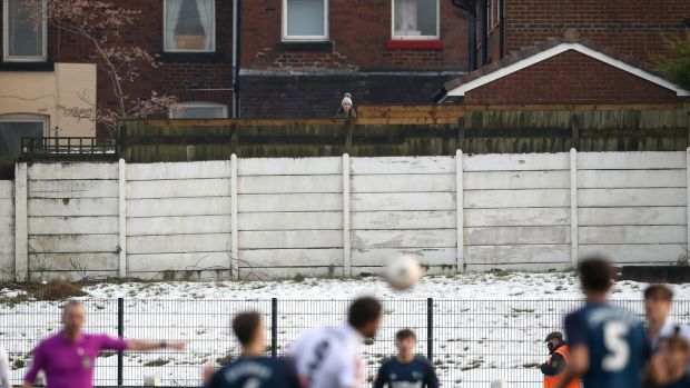 A spectator watches the game from behind a fence. Photo: Martin Rickett/PA Wire