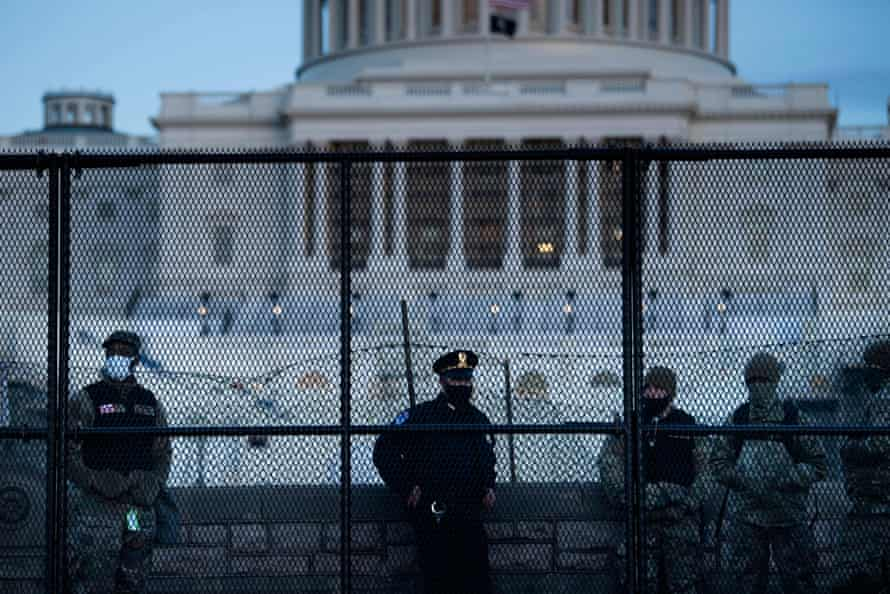 A Capitol police officer and members of the national guard stand near a fence surrounding the Capitol.