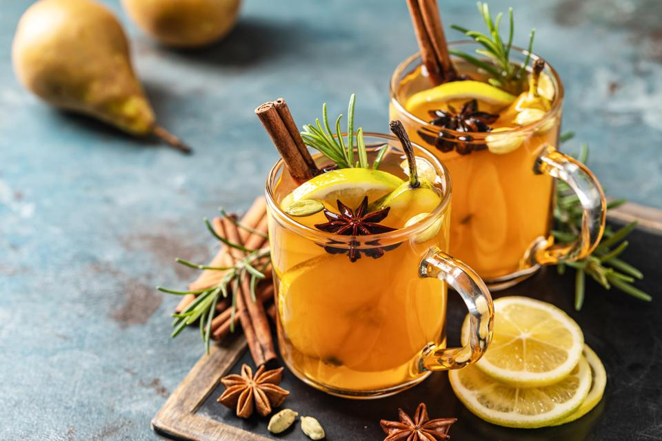 Hot drink cocktail for New Year, Christmas, winter or autumn holidays. Toddy. Mulled pear cider or spiced tea or grog with lemon, pear, cinnamon, anise, cardamom, rosemary.