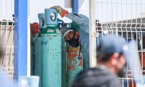A worker offloads oxygen cylinders in Queretaro, Mexico, on 21 Jan 2021.