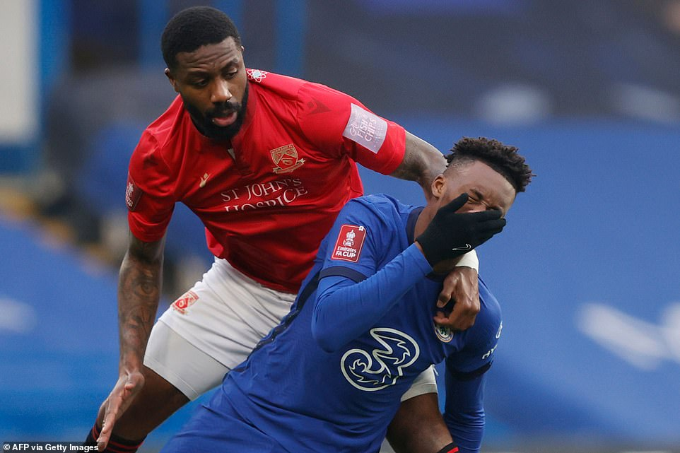 Hudson-Odoi goes down holding his face after a coming together with Morecambe's Cameroonian defender Yann Songo'o
