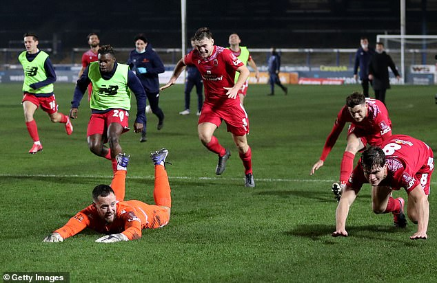 The goalkeeper leads the sliding celebrations with his team-mates after the second round win
