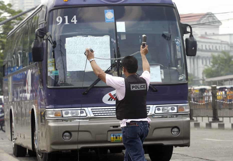 A police negotiator offers a telephone to a hostage taker on a bus in Manila in the Philippines in 2007.