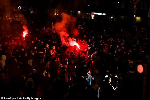 Fans set of flares while crowding together as they waited for teams to arrive on Tuesday