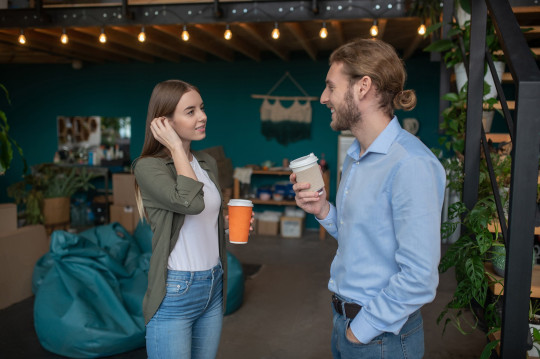 A man and a woman chatting and drinking coffee.