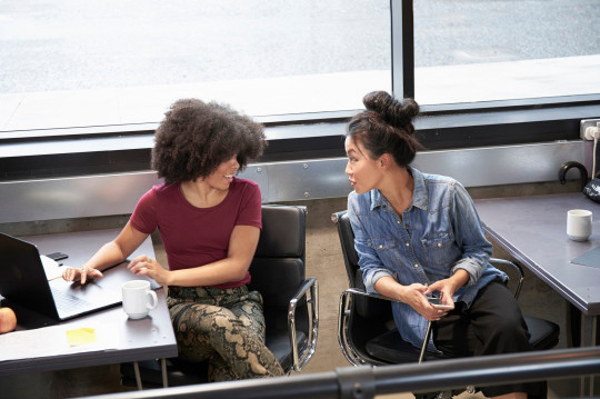 Women speaking together in office setting
