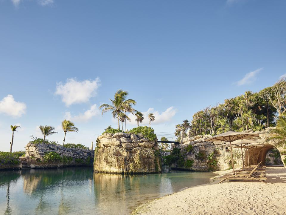 A beach with sand colored sunbeds and umbrellas next to a calm lagoon. In the background are small but tall rock islands topped with palm trees and connected by pedestrian bridges.