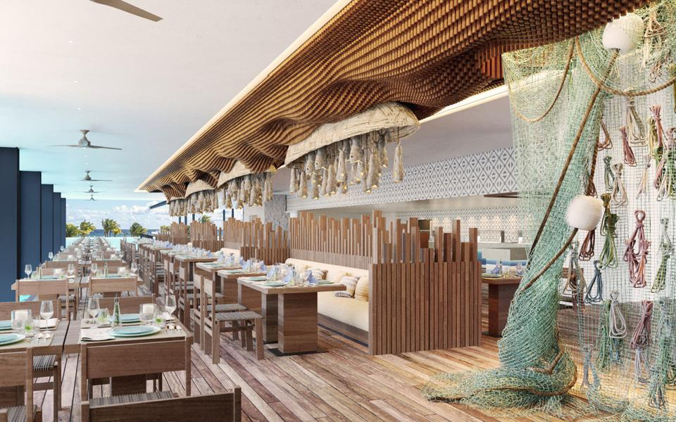 A long dining room with wooden floors and tables, decorated with fish nets. The ocean is in the background.