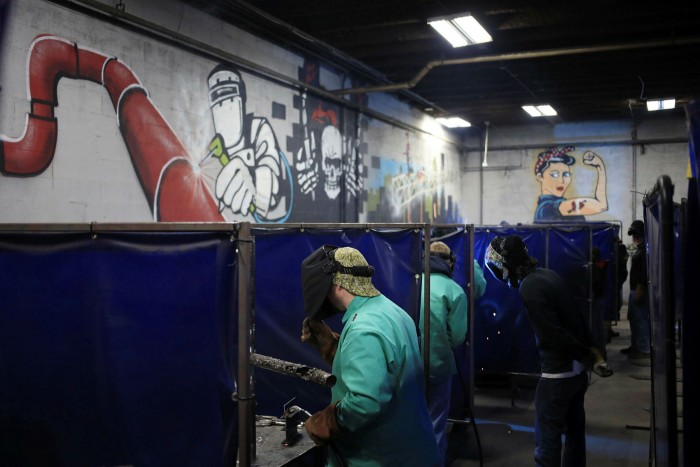 Students practice welding at a school in Louisville, Kentucky. Biden's Build Back Better plan could cost more than $3tn in areas ranging from infrastructure and climate change, to childcare, healthcare and education