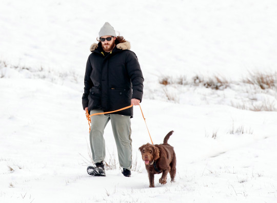 People walk a dog in snowy conditions near Hawes, in the Yorkshire Dales National Park, following fresh snow fall. Picture date: Saturday March 13, 2021. PA Photo. Photo credit should read: Danny Lawson/PA Wire