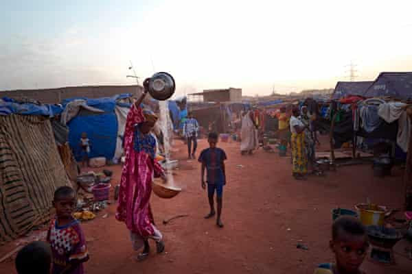 A Fulani woman sifts grain in a camp for displaced people in Bamako by a landfill site.