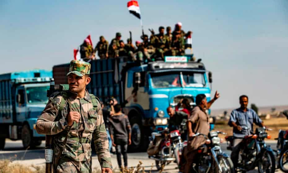 A Syrian government soldier with rifle on soldier in the foreground, with a truck full of troops and a motorcycle escort behind.