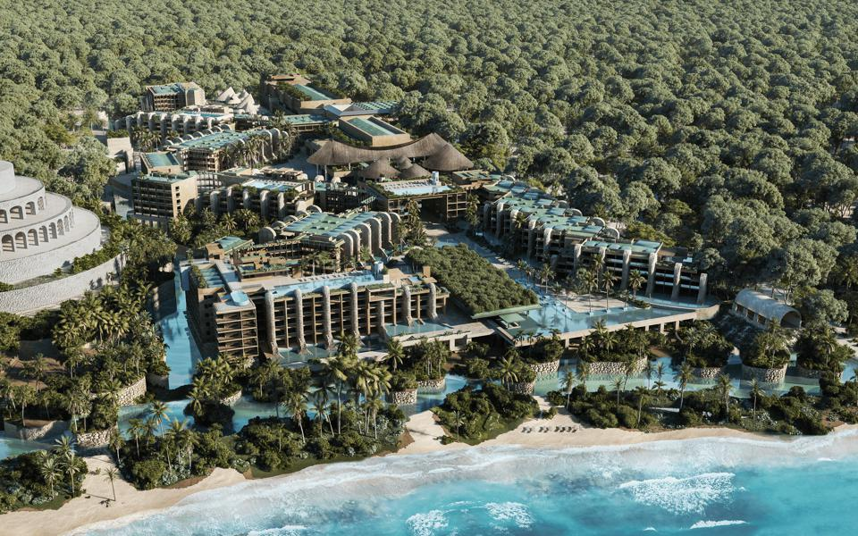 Shot from above with the ocean and beach in the foreground are several buildings, some topped by pools, surrounded by lagoons and trees.