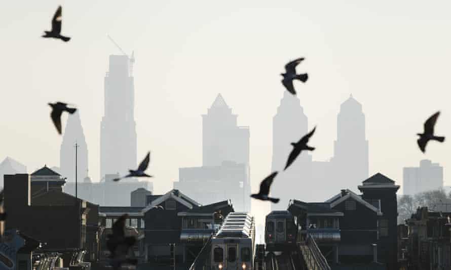 Birds fly over trains along the Market-Frankford Line in Philadelphia.